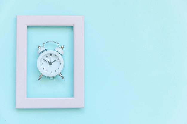 Tocar o sino duplo vintage despertador no quadro rosa isolado no fundo azul colorido pastel moderno