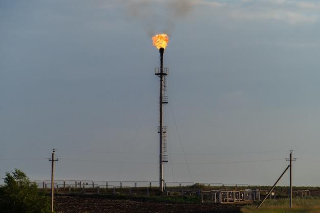 Tocha de gás de fogo de refinaria contra o céu cinzento