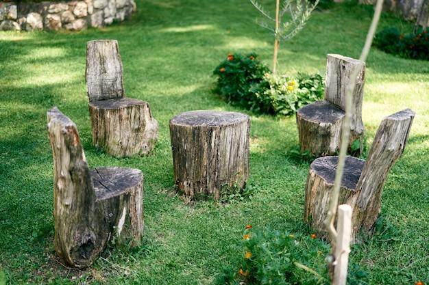 Tocos em forma de cadeiras e suporte de mesa em um prado verde
