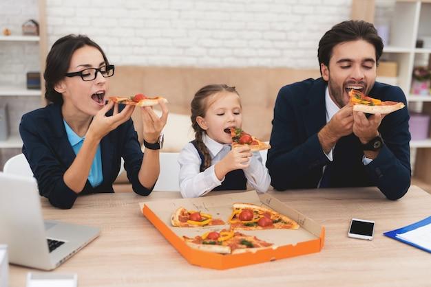 Toda a família come pizza em casa com prazer.
