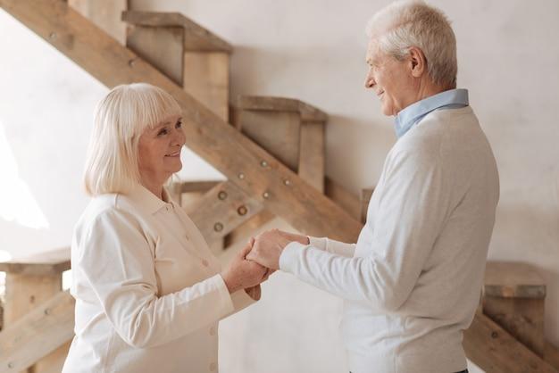 Toda a vida juntos. casal de idosos encantados e alegres, de pé frente a frente e de mãos dadas enquanto sorriem