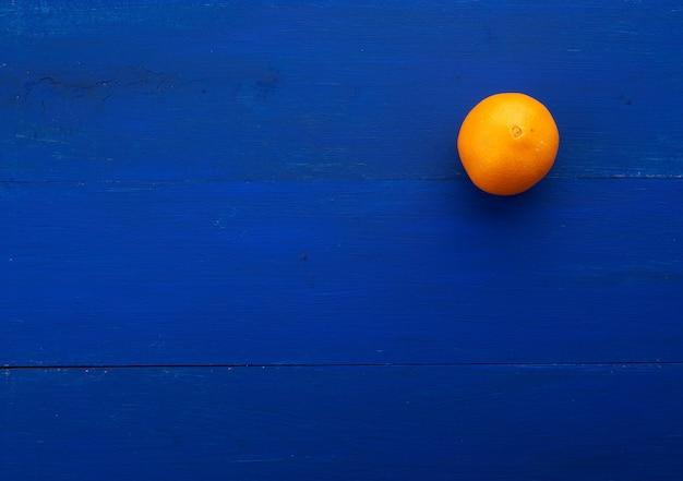 Toda laranja redonda laranja sobre fundo azul escuro de placas