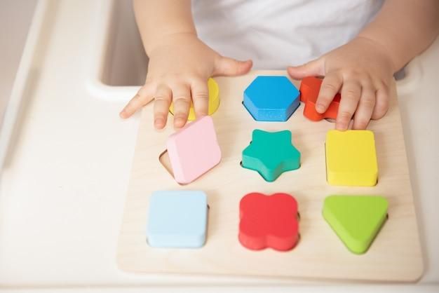 Toddler organiza e classifica os brinquedos por cor e forma geométrica. brinquedos de madeira educativos e de desenvolvimento. jogos montessorianos