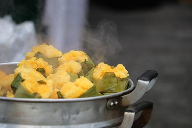 Toddy palm cake cor amarela na banana deixar com vapor cozinha da ásia