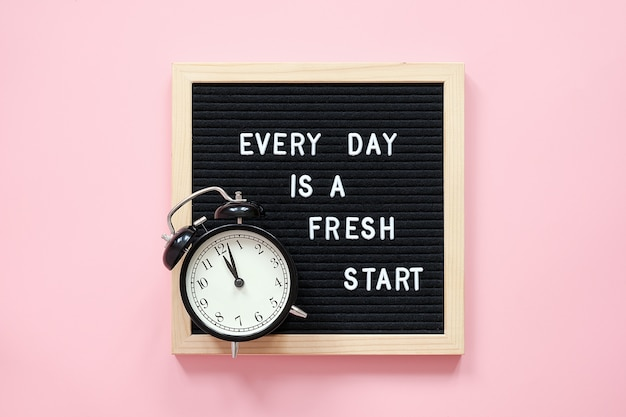 Todo dia é um novo começo. citação motivacional no quadro de letra preto e despertador preto sobre fundo rosa. inspiradora citação de conceito do dia. cartão postal