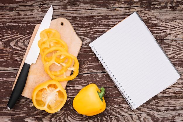 Todo e corte o pimentão amarelo na tábua de cortar com faca e espiral o bloco de notas na mesa de madeira