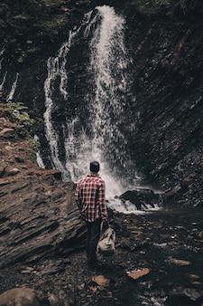 Todos deveriam ver. vista traseira de corpo inteiro de jovem olhando para a cachoeira durante uma caminhada nas montanhas