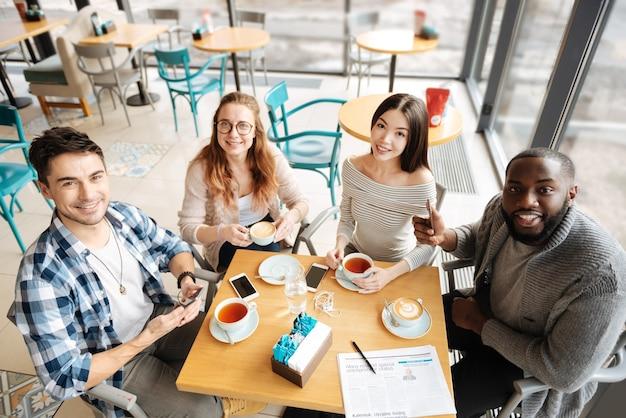 Todos juntos. vista superior de bons jovens felizes durante sua reunião no café.