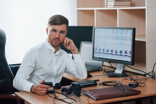 Todos mentem. o examinador de polígrafo trabalha no escritório com seu equipamento