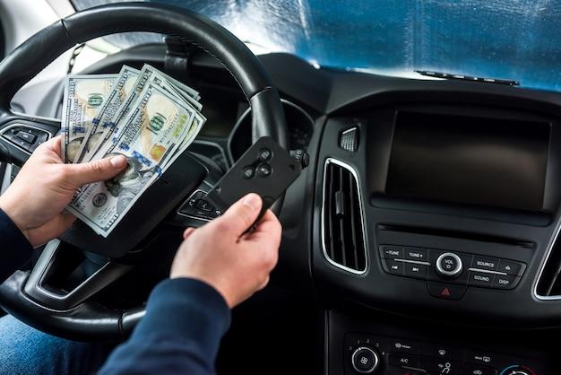 Todos para viagem automóvel dólar e chave do carro no conceito de finanças de mão masculina