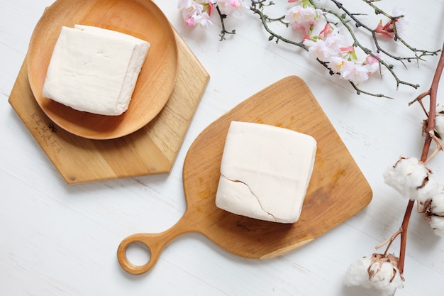 Tofu cru branco na placa de madeira marrom e mesa branca com flor de sakura