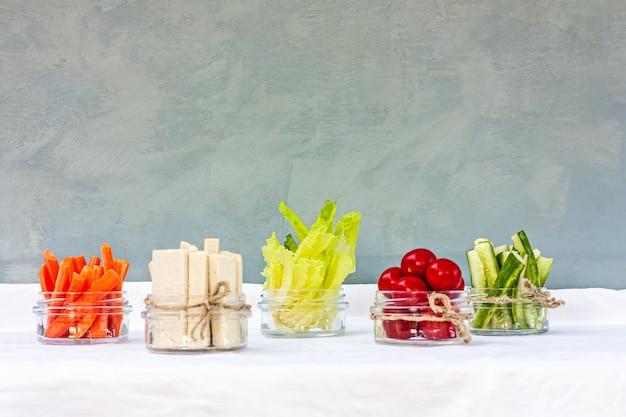 Tofu e vegetais diversos servidos em copos de vidro como lanche para um café da manhã saudável.
