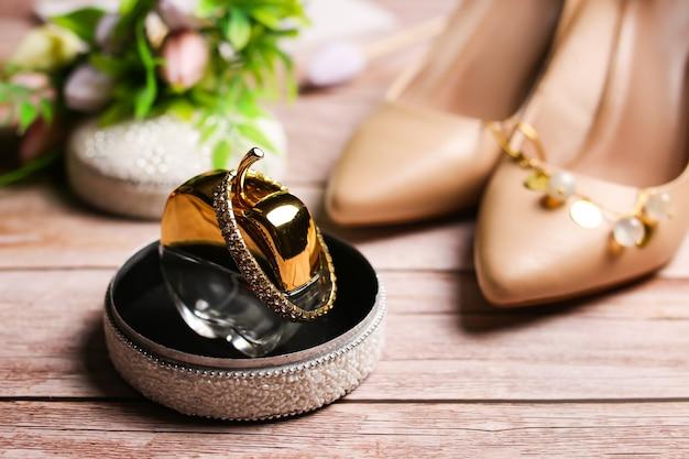 Toilete em forma de garrafa em forma de maçã, pulseira de ouro com pedras preciosas em uma caixa. saltos bege.