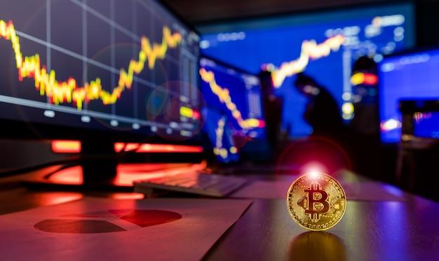 Token de criptomoeda bitcoin dourado com alargamento na mesa na frente gráfico de análise financeira, relatório de crescimento comercial na tela do computador e do laptop, enquanto o corretor se encontra na sombra de fundo desfocado.