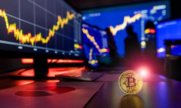 Token de criptomoeda bitcoin dourado com flare na mesa na frente do gráfico de análise financeira