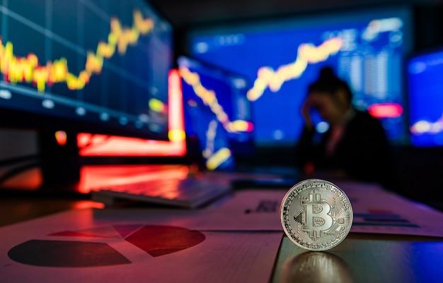 Token de criptomoeda bitcoin dourado na mesa em frente ao gráfico de análise financeira, relatório de crescimento comercial na tela do computador e do laptop, enquanto o corretor se encontra na sombra de fundo desfocado.