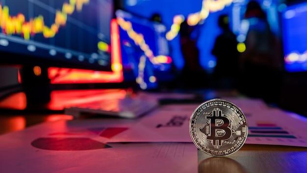 Token de criptomoeda bitcoin dourado na mesa na frente do gráfico de gráfico de análise financeira