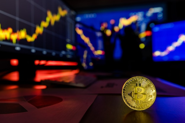 Token de criptomoeda bitcoin dourado na mesa na frente gráfico de análise financeira, relatório de crescimento comercial na tela do computador e do laptop, enquanto o corretor se encontra na sombra de fundo desfocado. Foto Premium