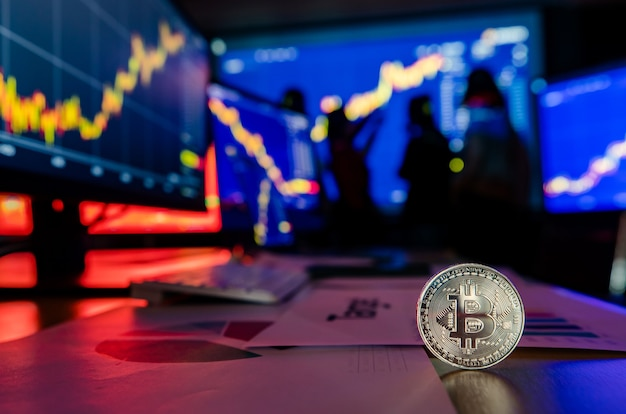 Token de criptomoeda bitcoin dourado na mesa na frente gráfico de análise financeira, relatório de crescimento comercial na tela do computador e do laptop, enquanto o corretor se encontra na sombra de fundo desfocado.