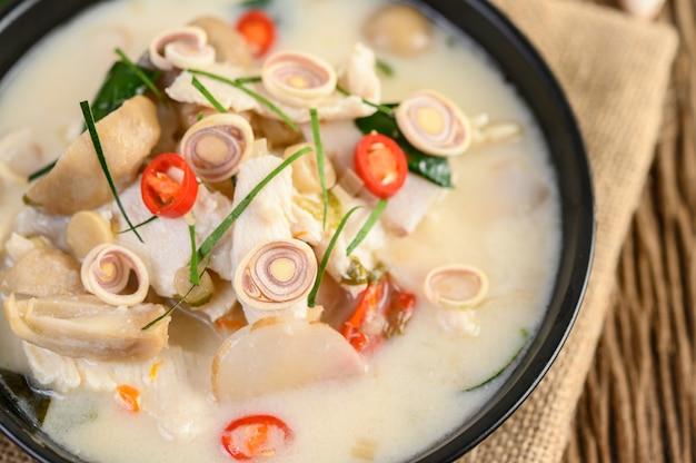 Tom kha kai numa frigideira com folhas de limão kaffir, erva-cidreira, cebola roxa, galanga e pimenta.