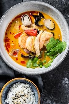 Tom yam kong ou tom yum, sopa clara e picante. fundo preto. vista do topo