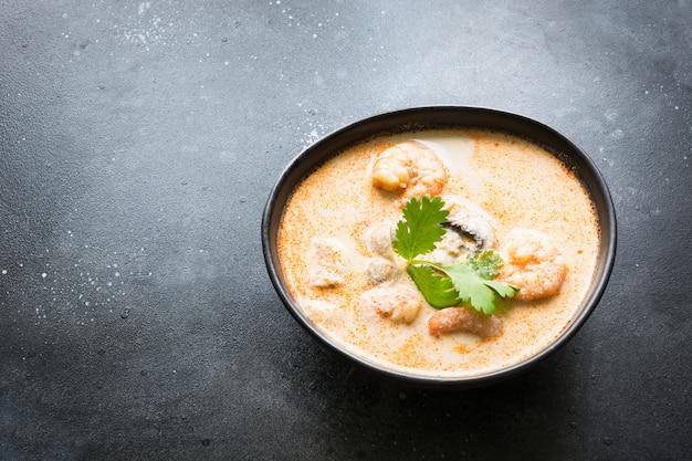 Tom yam kung sopa tailandesa picante com camarão, frutos do mar, leite de coco e pimenta. copie o espaço