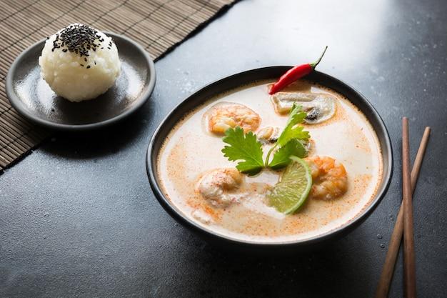 Tom yam kung sopa tailandesa picante com camarão, frutos do mar, leite de coco, pimenta e arroz.