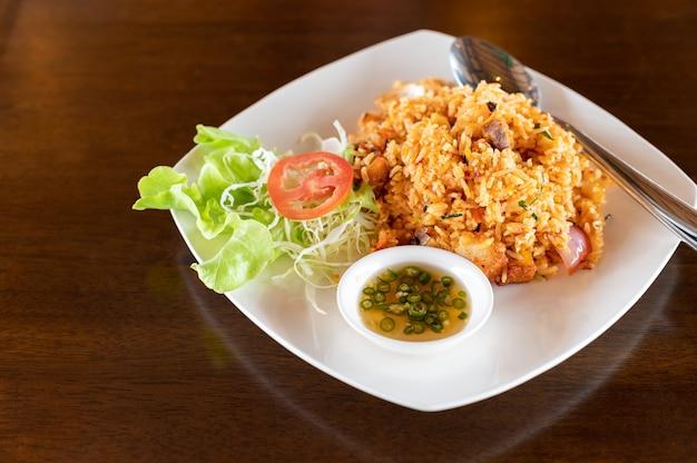 Tom yum arroz frito com carne de porco crocante na mesa de madeira