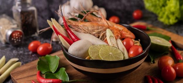 Tom yum kung em uma tigela com folhas de tomate, pimentão, capim-limão, alho, limão e lima kaffir