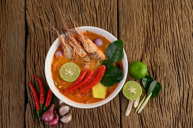 Tom yum kung thai sopa de camarão picante com capim-limão, limão, galanga e pimenta na mesa de madeira, tailândia