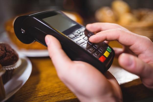Tomada ao cliente o pagamento através do terminal de pagamento no balcão
