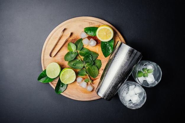 Tomada de coquetel de mojito. hortelã, limão, limão, ingredientes de gelo e utensílios de bar.
