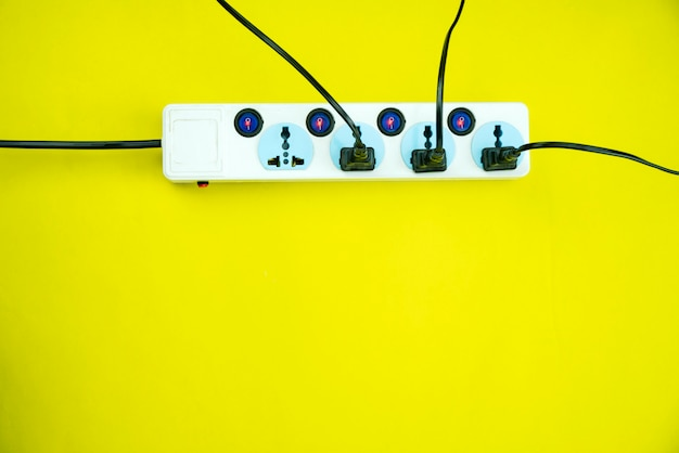 Tomada de energia elétrica e plugue em fundo de papel amarelo