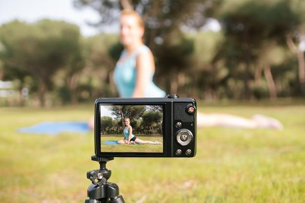 Tomada dos bastidores de um jovem influenciador vlogging. mulher bonita e madura gravando um vídeo de fitness e esporte para redes sociais falando diretamente para a câmera.