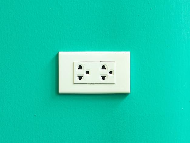 Tomada elétrica branca montada na parede verde