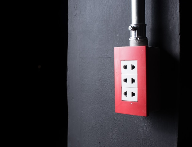 Tomada elétrica na parede, sobre fundo escuro
