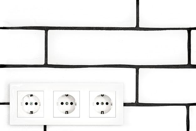 Tomadas elétricas contra uma parede de tijolos brancos.
