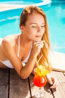 Tomando banho de sol. mulher jovem e bonita de biquíni branco deitada à beira da piscina com coquetel e de olhos fechados