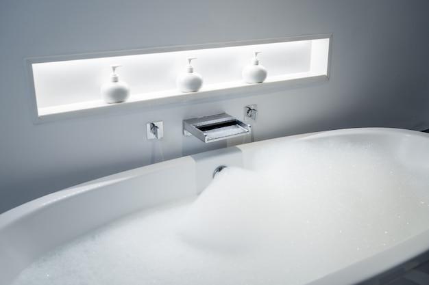 Tomando banho na banheira e jogando bolhas de sabão na sala de banho.