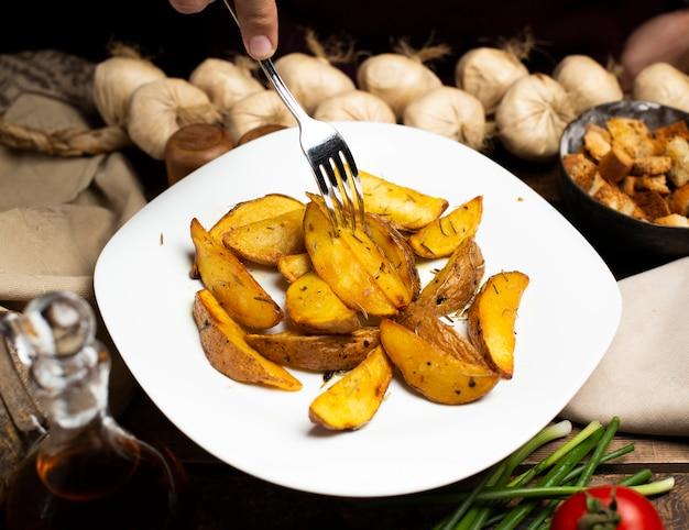 Tomando batatas fritas do prato branco por um garfo