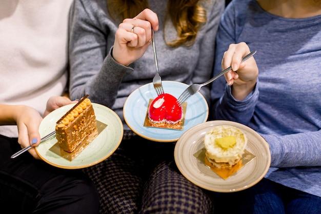 Tomando café e comendo sobremesas juntos. vista superior das mãos de três belas mulheres segurando placas com sobremesas deliciosas bolos no café. encontro de melhores amigas. café com bolos