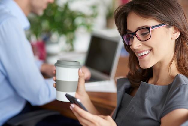 Tomando café e usando o celular