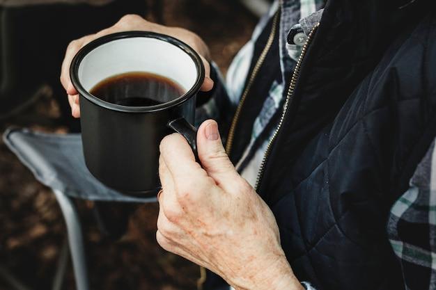 Tomando café perto da barraca na floresta