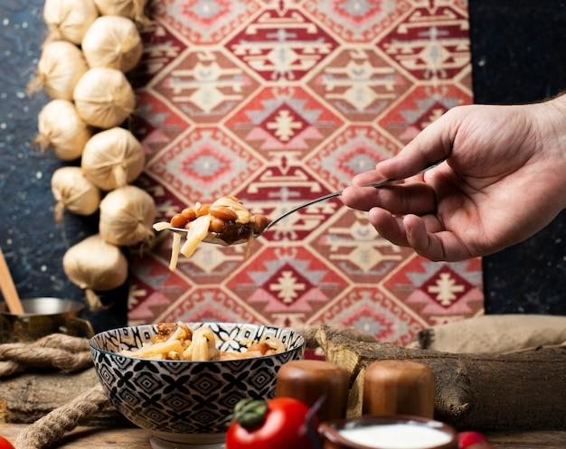 Tomando macarrão de feijão da tigela com colher. decoração de estilo étnico.
