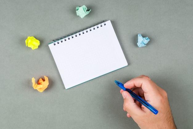 Tomando notas conceito com caderno, notas rasgadas na opinião superior do fundo cinza. caneta de exploração de mão. espaço para texto. imagem horizontal