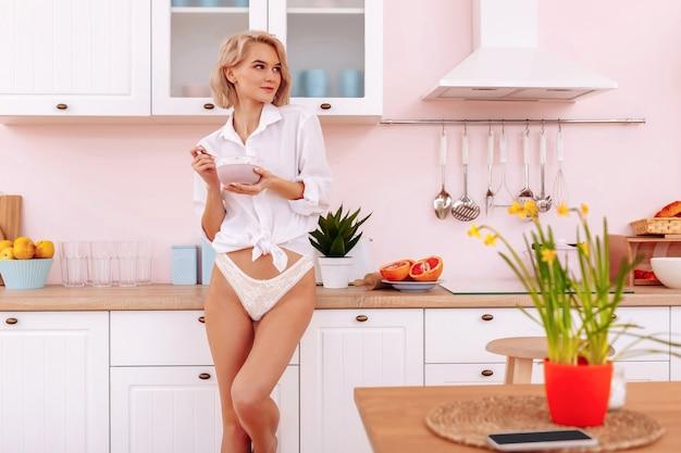 Tomando o café da manhã. mulher jovem e bonita de calcinha e camisa branca em pé na cozinha tomando café da manhã
