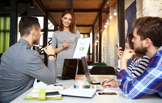Tomando ótimas decisões. jovem mulher bonita gesticulando e discutindo algo com sorriso, enquanto seus colegas de trabalho a ouvem sentada à mesa do escritório.