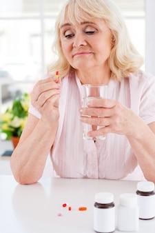 Tomando remédios. mulher idosa deprimida segurando a pílula na mão e olhando para ela enquanto está sentada à mesa