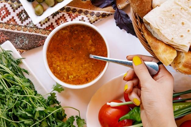 Tomando sopa de beterraba russa com uma colher.