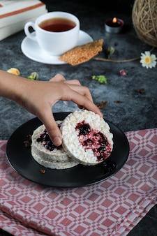 Tomando um biscoito com geléia vermelha